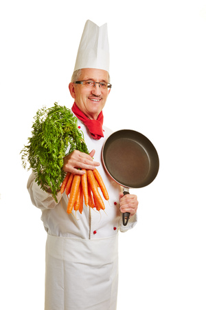 Happy chef cook in workwear with frying pan and carrots