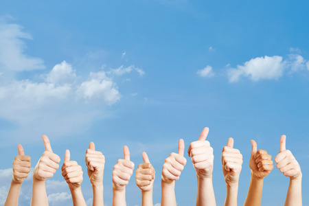 Many hands over the sky with thumbs up as motivation
