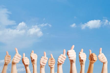 Viele Hände über den Himmel mit Daumen nach oben als Motivation Standard-Bild - 65066486