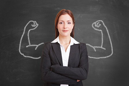 self assurance: Succesful self confident businesswoman with muscles drawn with chalk on a blackboard