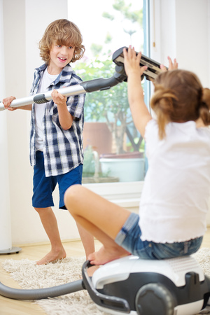 suck: Boy and girl playing with vacuum cleaner while doing housecleaning Stock Photo