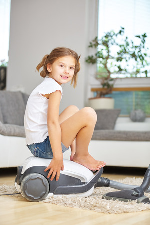 suck: Happy girl sitting on vacuum cleaner and playing at home Stock Photo