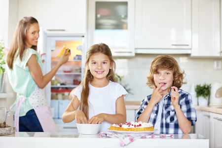 prepare: Mother and two children baking and tasting a fruit cake in the kitchen