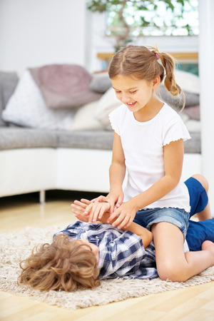 romp: Two kids playing and romping at home in the living room