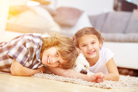 affections: Two happy kids play at home with a Golden Retriever dog