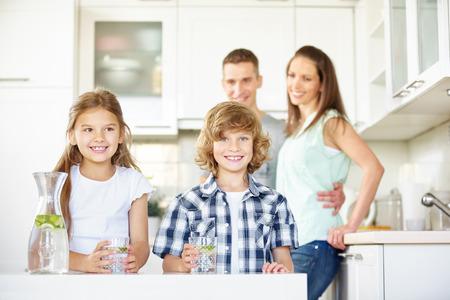 Kinderen in de keuken met vers water met limoenen terwijl de ouders kijken