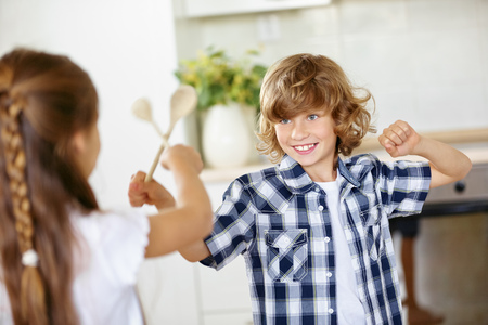 sibling rivalry: Two children fighting in jest in the kitchen with wooden spoons