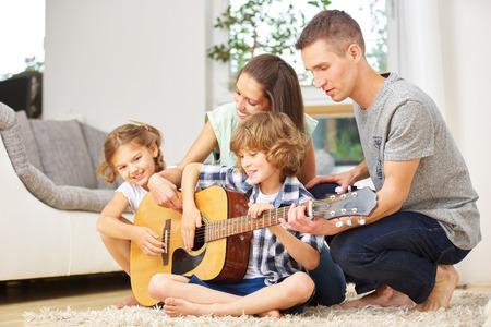 Família fazendo música com violão em casa, na sala de estar Foto de archivo
