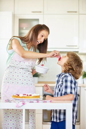 childrens food: Mother and son baking fruit cake together in kitchen with red currants