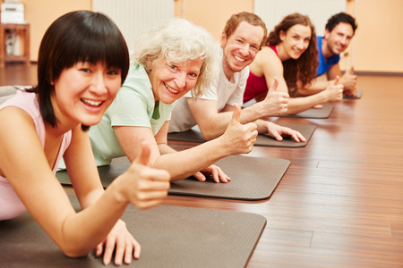 Group of people with senior woman and thumbgs up at fitness studio