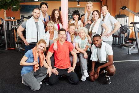 heureux groupe de personnes à la salle de gym avec un entraîneur et les femmes âgées