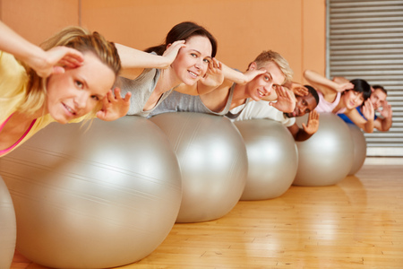 gym ball: Group training their back with gym ball during pilates