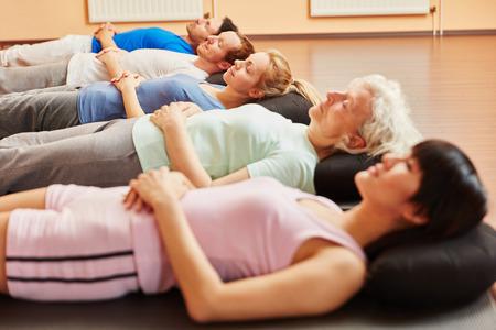 Senior y grupo durante ejercicios de respiración para la relajación en clase de yoga