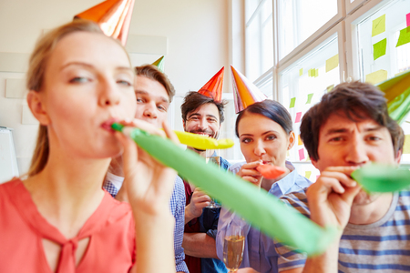 office party: Group of students celebrating with noisemakers in party