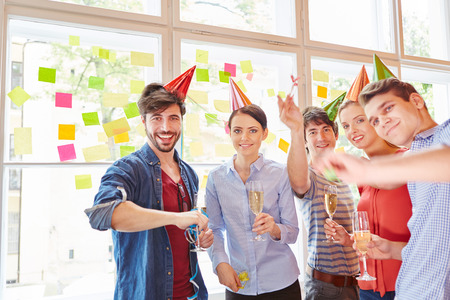 office party: Start- up team celebrating success with party drinking sparkling wine Stock Photo