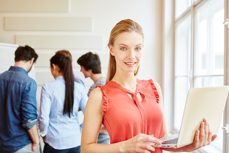 learning computer: Young businesswoman with laptop in front of her business start-up team Stock Photo