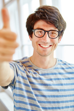 Successful man as student holding thumbs up Stock Photo