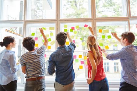napsat: Mladí studenti na semináři brainstormingu s barevnými poznámkami