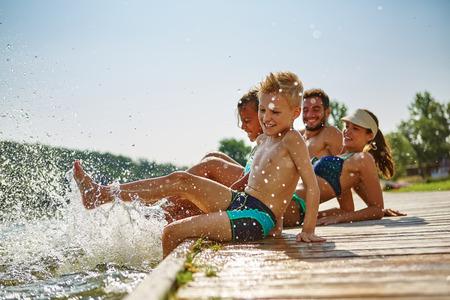 湖畔に自分の足で楽しさと水しぶき水を持っている幸せな家族