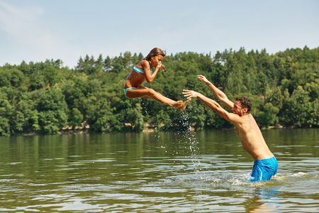 nonsense: Father in the lake throwing his daughter into the water and having fun in summer Stock Photo