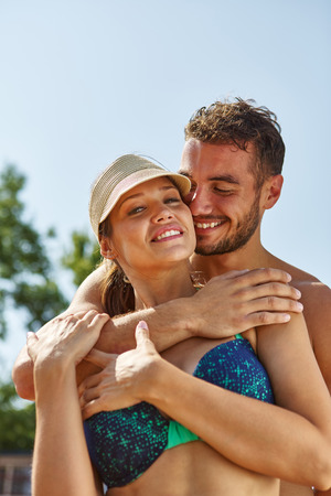 Couple laughs and hugs happily on their summer holidays