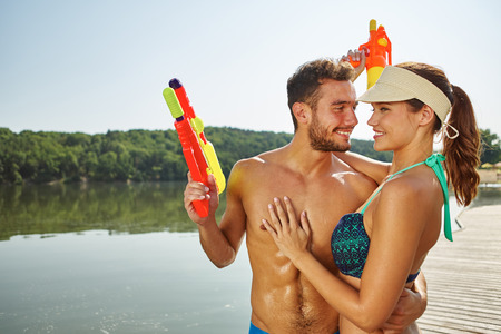 Happy couple in love at a lake with squirt guns hugging each other Stock Photo