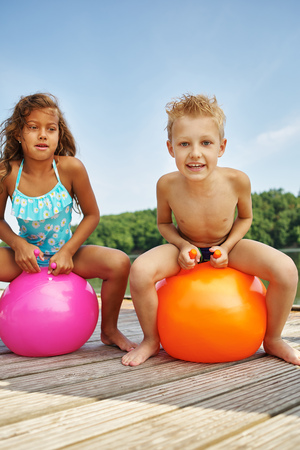 child ball: Two happy children sitting on a spacehooper at a lake in summer