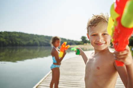 woman squirt: Kid with a squirt gun at a lake spraying his sister with water Stock Photo