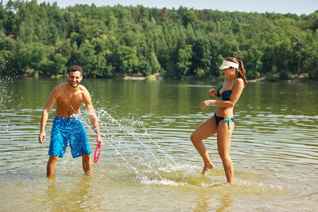 romp: Happy couple splashes and sprays each other with water