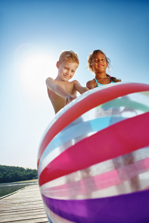 lake beach: Two kids at a lake playing with a beach ball during the summer holidays
