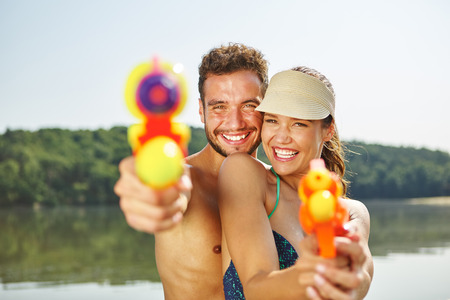 Couple aiming with water guns in summer and having fun on their holiday