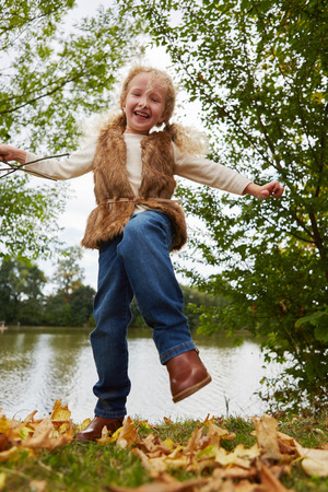 romp: Gril having fun and dancing on leaves in autumn at the park Stock Photo