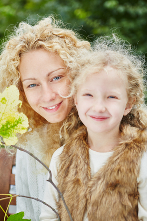 daugther: Mother and daugther with blond curly hair happily looking in the camera and smiling