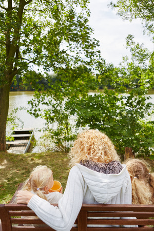 single mother: Single mother with two children sitting on bench
