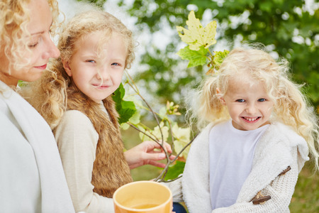 sibling: Family with two sibling girls in garden in autumn
