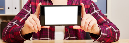 phone business: Hands of a woman holding a smartphone with an empty touchscreen