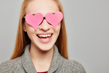 Smiling woman with two pink hearts on her glasses