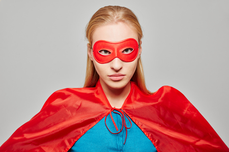 superheroine: Young blond woman dressed as a superhero with a mask and a cape looking serious
