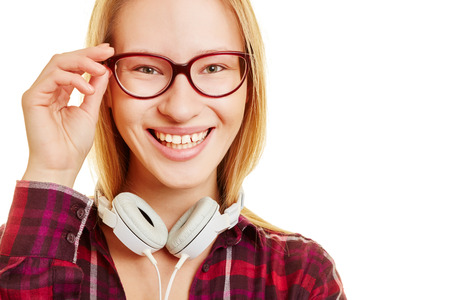 nearsighted: Young girl smiles and holds her hand on her glasses