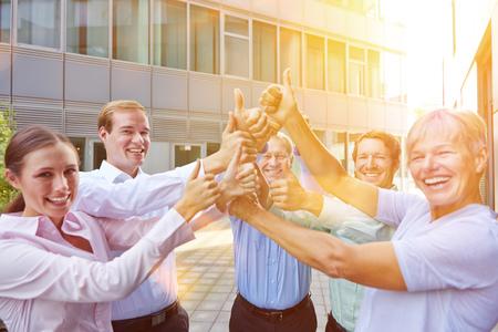 Glückliche Geschäftsleute team das Halten von Daumen oben im Sommer Standard-Bild - 63538475