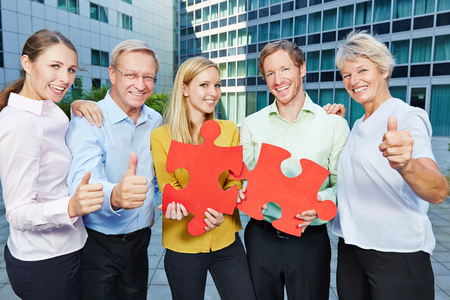 Successful business people with big red jugsaw puzzle pieces holding thumbs up photo