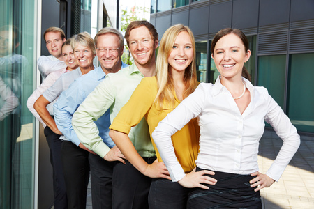 work group: Happy business people team standing in a row outside the office Stock Photo