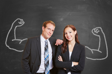 self assurance: Blackboard with businesswoman and businessmann couple with chalk muscles Stock Photo