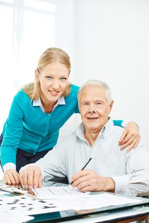testament schreiben: Familie mit älteren Mannes Kreuzworträtsel zu Hause für das Gedächtnistraining zu lösen Lizenzfreie Bilder