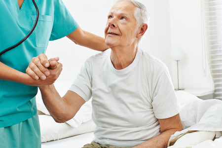 Geriatric caregiver helping old man getting up from bed Stock Photo