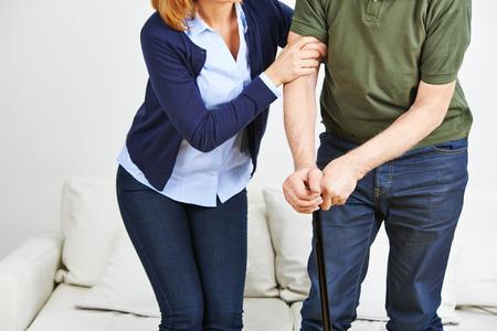 levantandose: Mujer apoyar hombre mayor con la caña de levantarse de un sofá