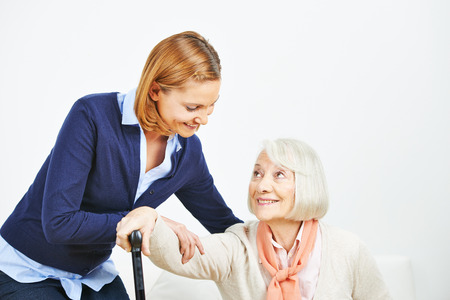 get help: Caregiver helping senior woman with cane getting up from a sofa
