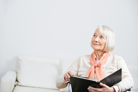 eldercare: Senior woman in a wheelchair with book looking pensive