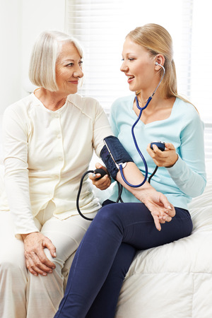 house call: Woman doing blood pressure monitoring for senior woman at home