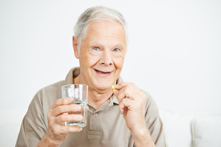 take a: Old man swallowing a pill with a glass of water